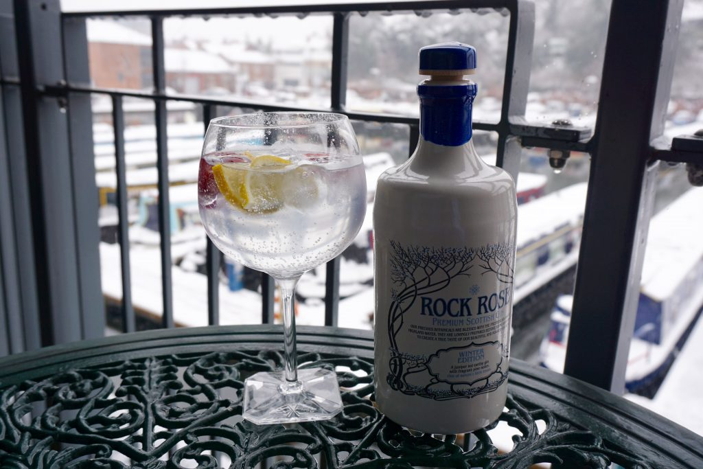 Rock Rose Gin Bottle next to Gin and Tonic