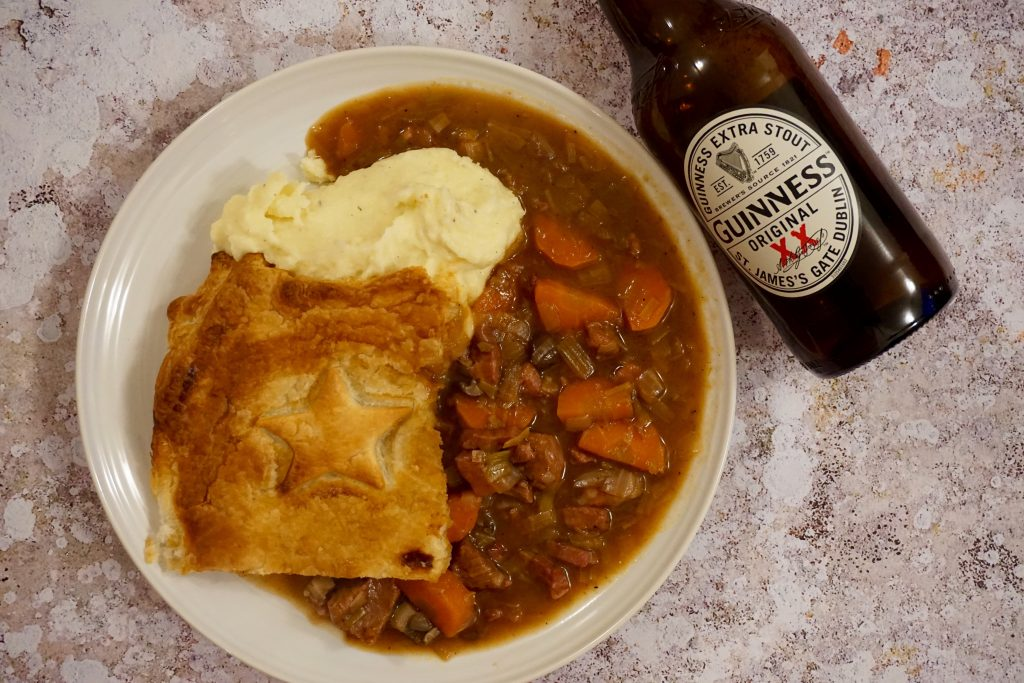 Steak and Guinness Pie Served With Mash On Plate and Bottle of Guinness