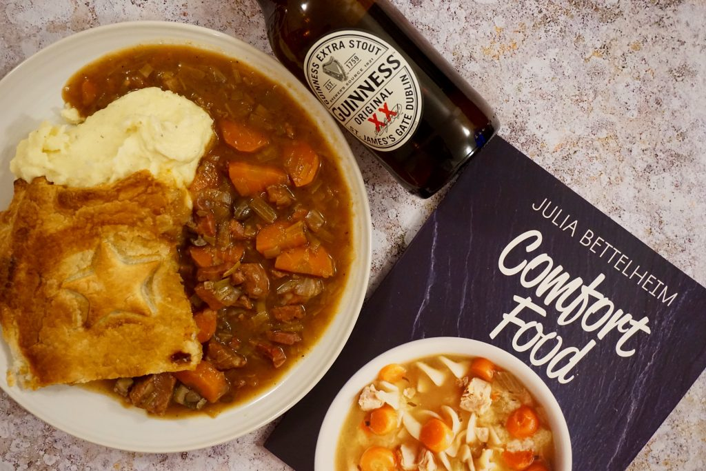 Steak and Guinness Pie Served With Mash On Plate and Bottle of Guinness Next to Comfort Food Recipe Book