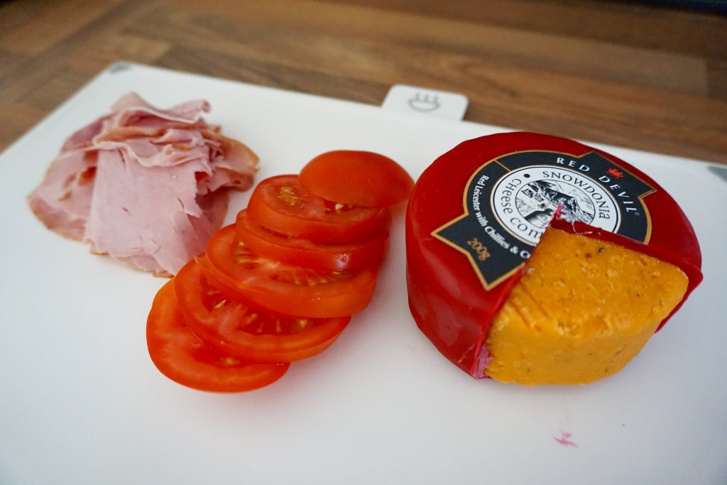 Snowdonia Red Devil Cheese, Ham and Tomato Sandwich - Ingredients on a chopping board